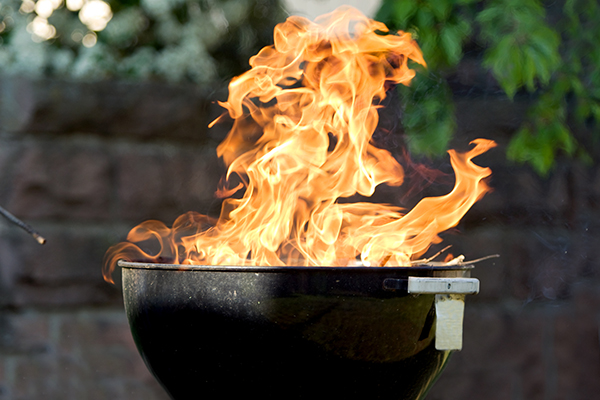 Raging fire from charcoal barbecue grill